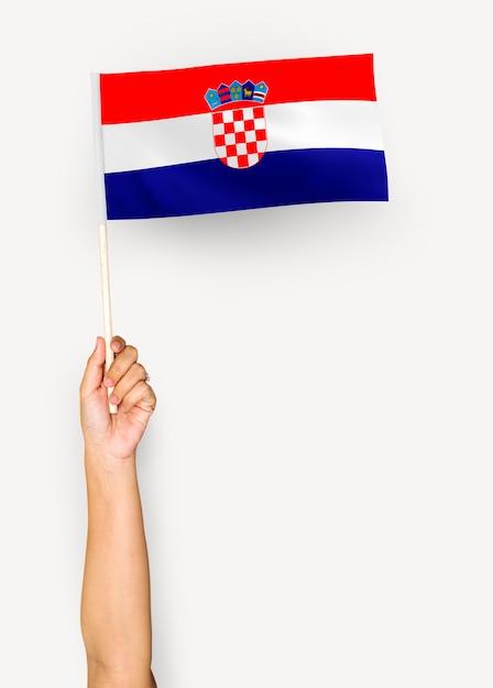 Pessoa acenando a bandeira da república da croácia Foto gratuita