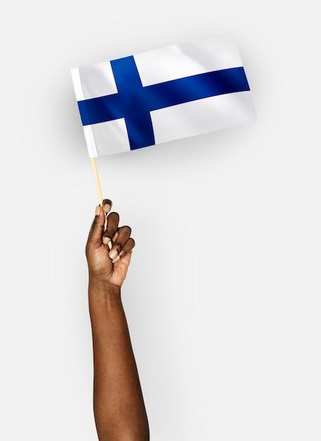 Pessoa acenando a bandeira da república da finlândia Foto gratuita