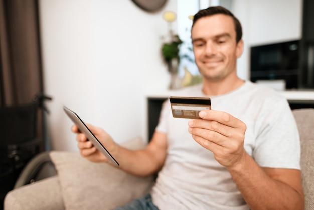Pessoa alegre possui cartão de crédito e usa tablet. Foto Premium