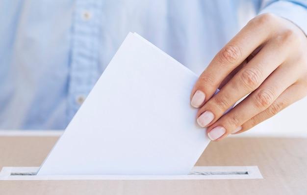Pessoa colocando a cédula vazia em uma caixa de close-up Foto gratuita