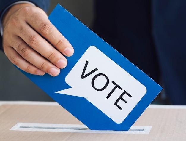 Pessoa colocando uma cédula em uma caixa de eleição Foto gratuita