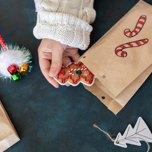 Pessoa colocando uma guloseima dentro de uma sacola de presente de natal decorada com bastão de doces Foto gratuita