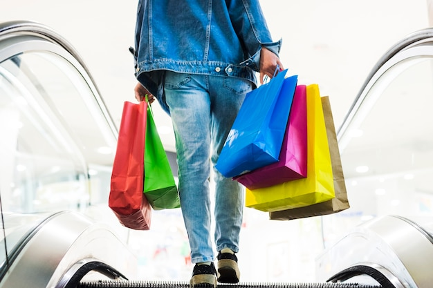 Pessoa, com, bolsas para compras, ligado, a, escada rolante Foto gratuita