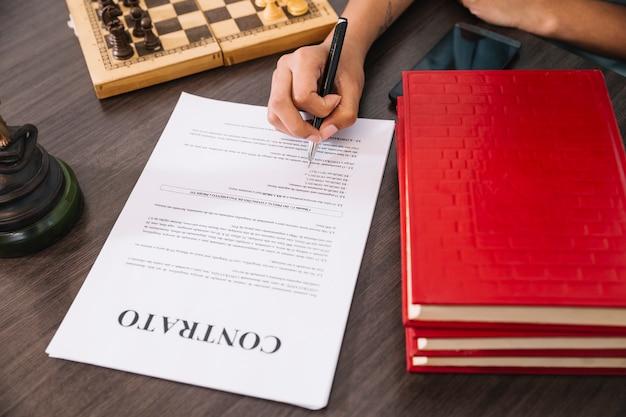 Pessoa com caneta escrevendo no documento na mesa com smartphone, livros e xadrez Foto gratuita