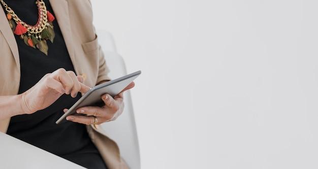 Pessoa com colar segurando um tablet com copyspace Foto gratuita
