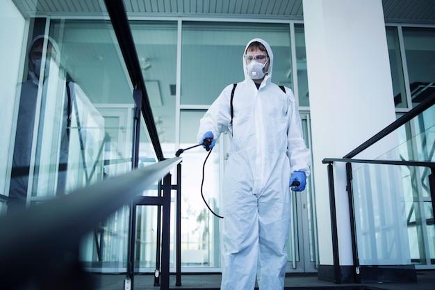 Pessoa com roupa de proteção química branca fazendo a desinfecção de áreas públicas para impedir a propagação do vírus corona altamente contagioso Foto gratuita