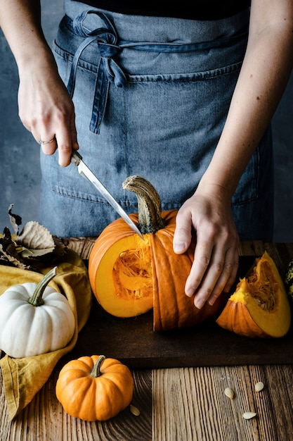 Pessoa cortando abóbora de halloween Foto gratuita