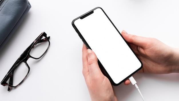Pessoa de alto ângulo, segurando um telefone vazio Foto gratuita
