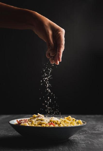 Pessoa de close-up, colocando o queijo no macarrão Foto gratuita