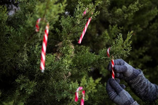 Pessoa de close-up com luvas para decorar a árvore de natal Foto gratuita