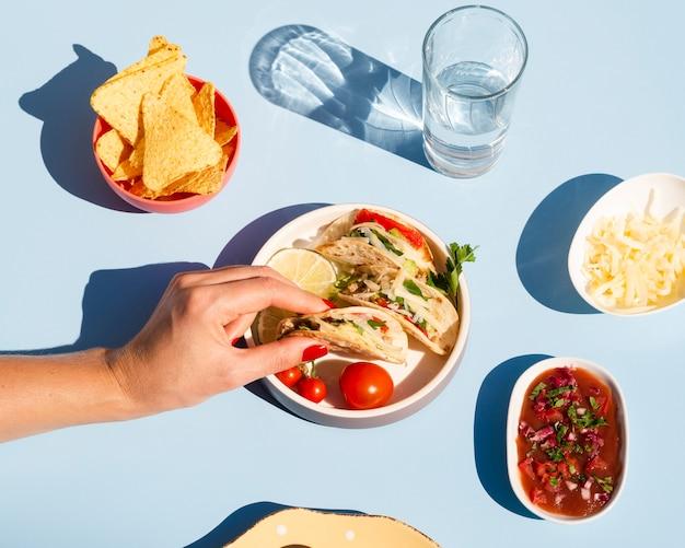 Pessoa de close-up com taco e molho delicioso Foto gratuita