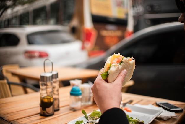 Pessoa de close-up comendo um hambúrguer Foto gratuita