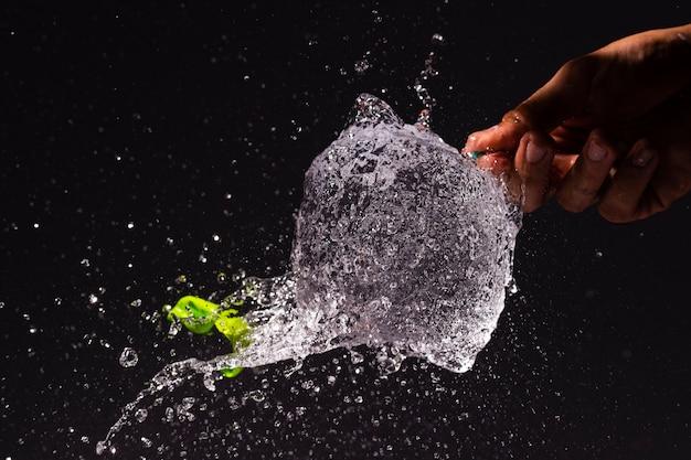 Pessoa de close-up estourando um balão de água Foto gratuita
