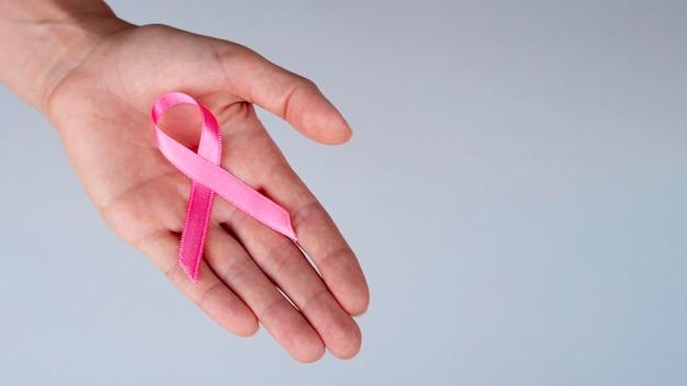 Pessoa de close-up, segurando a fita rosa Foto gratuita