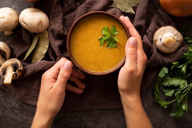 Pessoa de close-up, segurando a tigela com sopa de abóbora Foto gratuita
