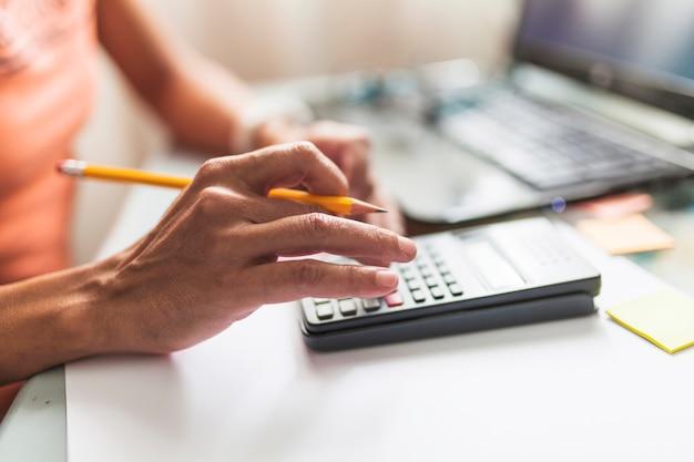 Pessoa de colheita fazendo cálculos perto de laptop Foto gratuita