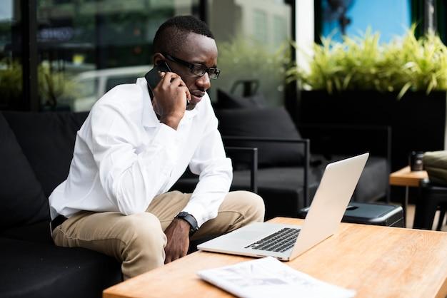 Pessoa de negócios afro-africano de descida de africano de telefone Foto gratuita