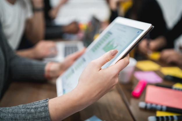 Pessoa de negócios criativos trabalhando em tablet digital e checando algumas informações no local de trabalho. conceito de tecnologia. Foto Premium