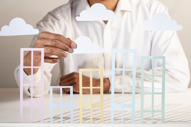 Pessoa de negócios e edifícios de papel e nuvens Foto gratuita