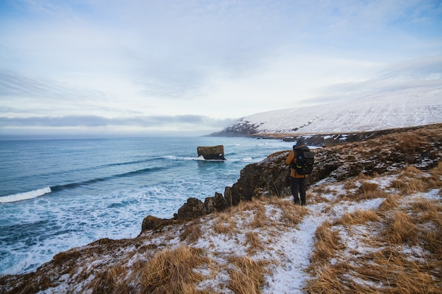 Pessoa de pé nas colinas cobertas de neve, cercadas pelo mar na islândia Foto gratuita