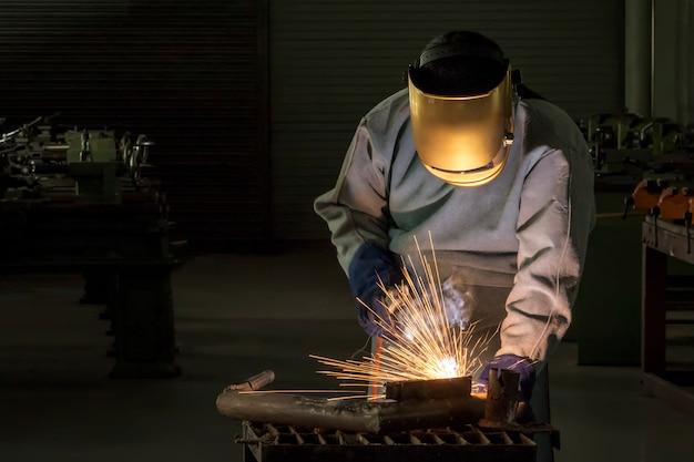 Pessoa de trabalho industrial no aço do soldador da fábrica Foto Premium