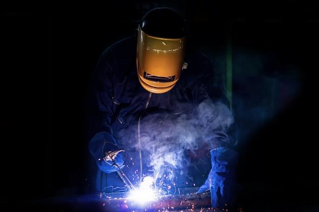 Pessoa de trabalho sobre o aço do soldador usando a máquina de soldadura elétrica. Foto Premium