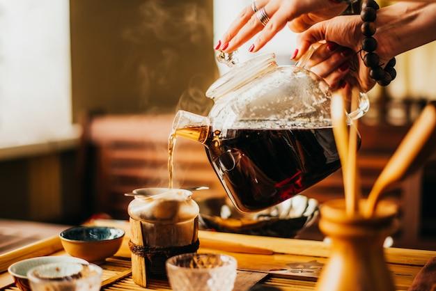 Pessoa derrama chá verde fresco no café Foto Premium