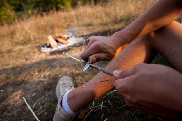 Pessoa esculpe uma vara de madeira ao ar livre Foto gratuita
