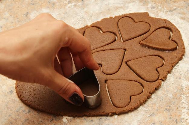 Pessoa fazendo biscoitos deliciosos em forma de coração Foto gratuita