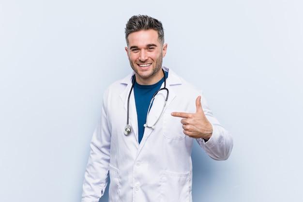 Pessoa jovem bonito médico homem apontando à mão para um espaço de cópia de camisa, orgulhoso e confiante Foto Premium