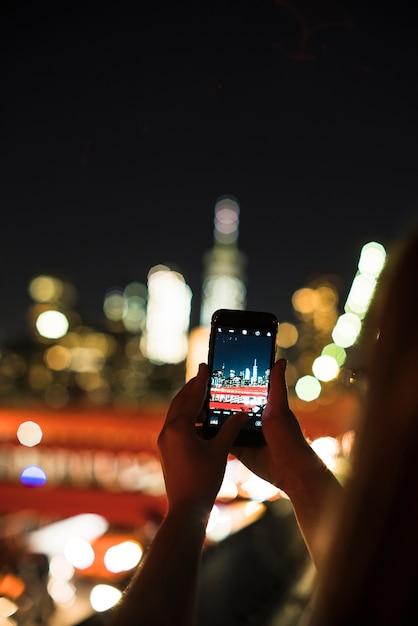 Pessoa, levando, foto, de, cidade noite, ligado, smartphone Foto gratuita