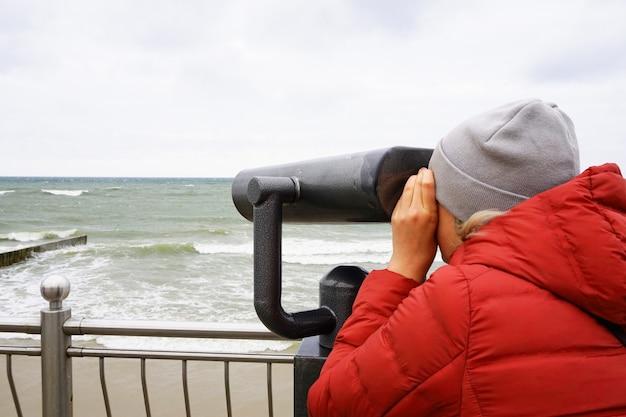 Pessoa olha através de um telescópio Foto Premium