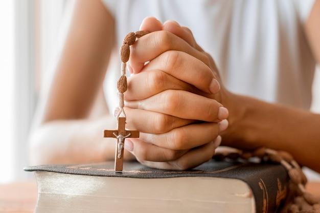 Pessoa orando com rosário Foto Premium