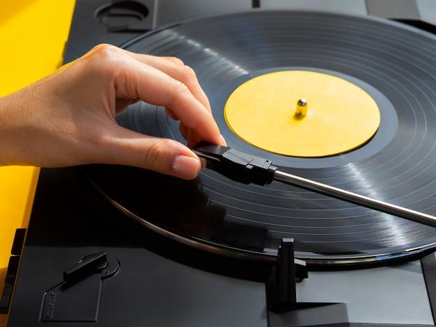 Pessoa que coloca o disco de vinil no player Foto gratuita