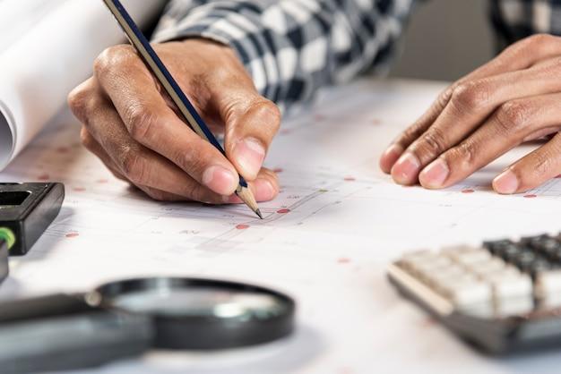 Pessoa que desenha uma planta de uma casa Foto gratuita
