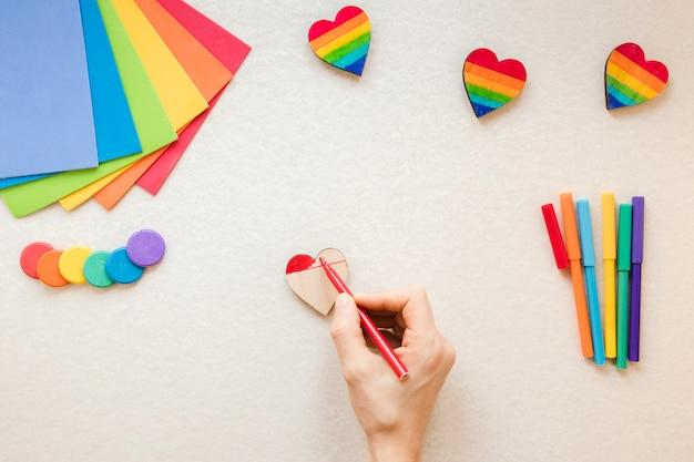 Pessoa que pinta o coração do arco-íris com caneta de feltro vermelho Foto gratuita