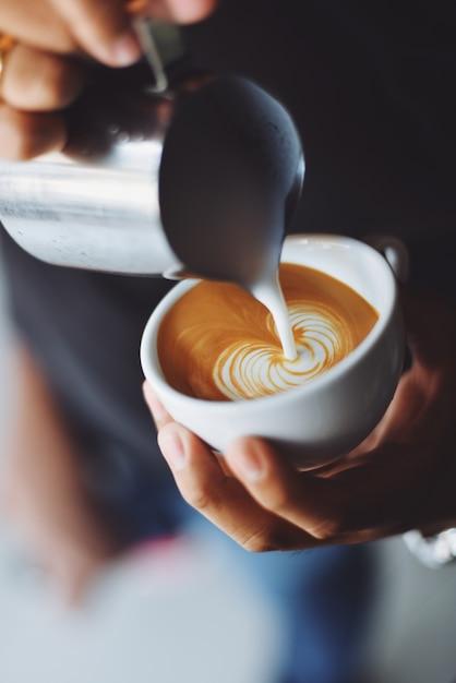 Pessoa que serve uma xícara de café Foto gratuita
