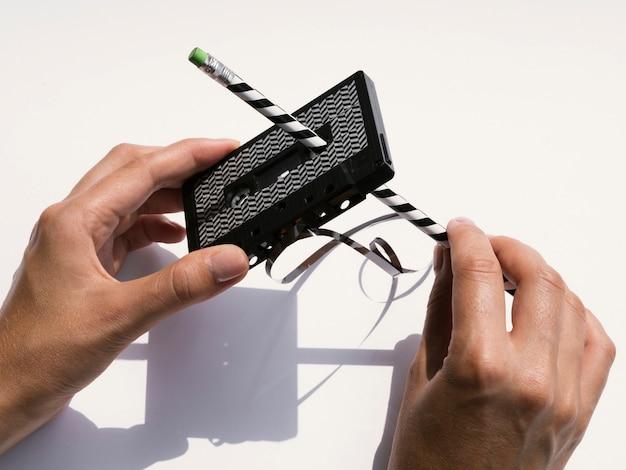 Pessoa reparando fita cassete preta com lápis Foto gratuita