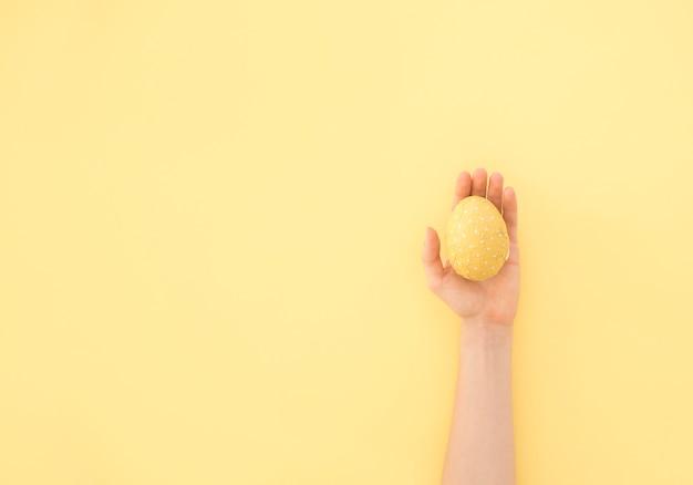 Pessoa, segurando, amarelo ovo páscoa, em, mão Foto gratuita