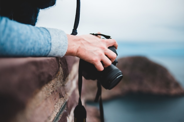 Pessoa, segurando, câmera preta Foto gratuita