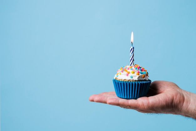 Pessoa, segurando, cupcake, com, vela acesa Foto Premium