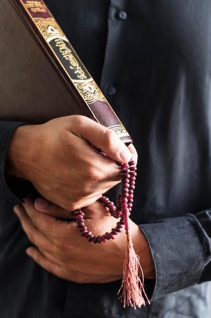Pessoa, segurando o rosário e livro religioso Foto gratuita