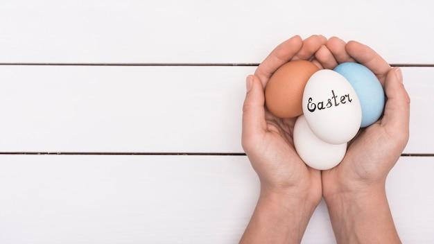 Pessoa segurando ovos coloridos com inscrição de páscoa Foto gratuita