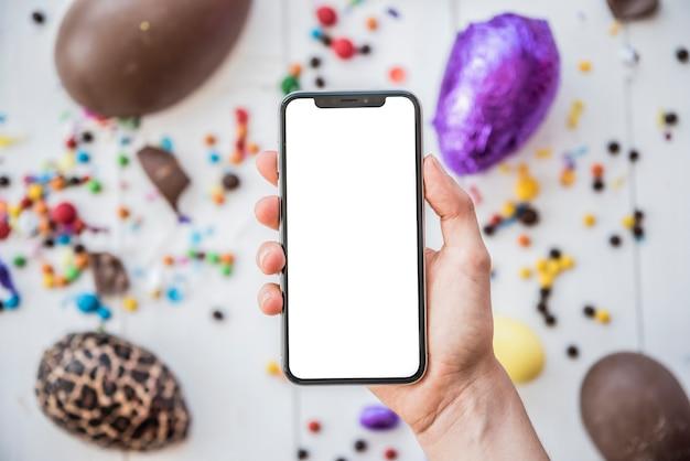 Pessoa, segurando, smartphone, com, em branco, tela, acima, ovos páscoa Foto gratuita
