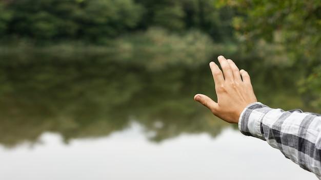 Pessoa, segurando sua mão acima do lago Foto gratuita