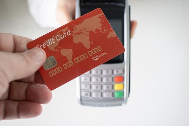 Pessoa segurando um cartão de crédito vermelho com um terminal de pagamento borrado ao fundo Foto gratuita