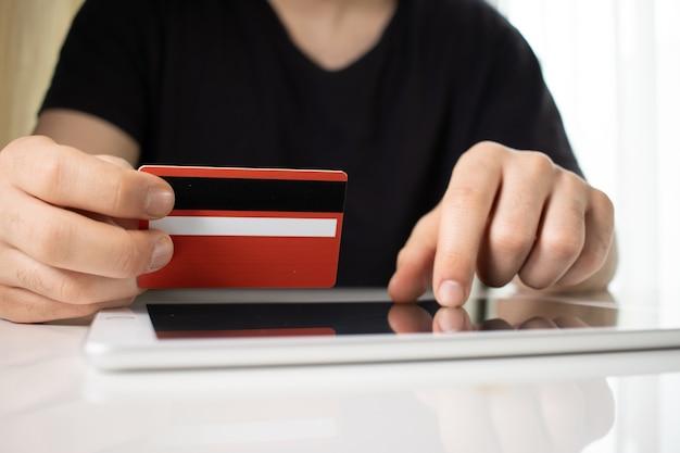 Pessoa segurando um cartão de crédito vermelho sobre um tablet em uma superfície branca Foto gratuita
