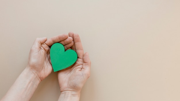 Pessoa, segurando um coração verde sobre fundo bege, com espaço de cópia Foto gratuita