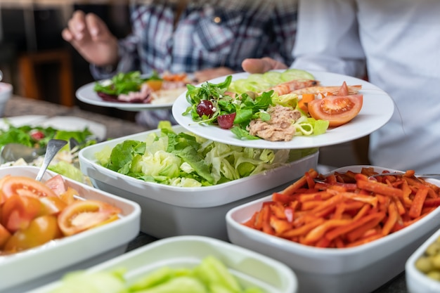 Pessoa, segurando um prato de salada na frente de um balcão de comida em um restaurante self-service Foto Premium