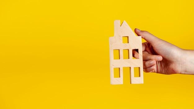 Pessoa, segurando uma casa de madeira com espaço de cópia Foto gratuita